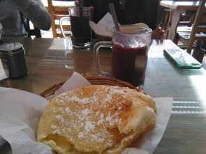 Having Api & Pasteles, a classic hot drink made from purple corn, and a cheese pastry