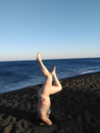 Practicing headstands on black sand